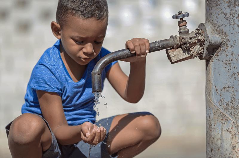 Kind an Wasserhahn - Wassermangel als Grund für eine vegane Lebensweise